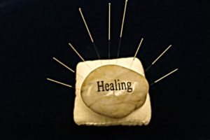 Healing stone on cushion with acupuncture needles